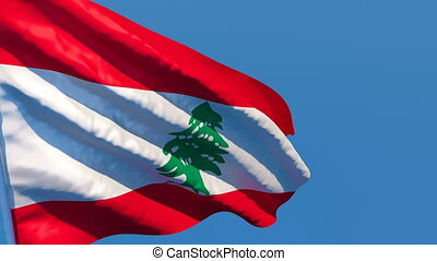 The national flag of Lebanon flutters in the wind against a blue sky