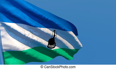 The national flag of Lesotho flutters in the wind against a blue sky