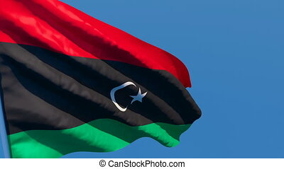 The national flag of Libya flutters in the wind against a ...