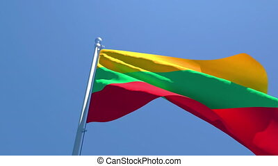 The national flag of Lithuania flutters in the wind against a blue sky