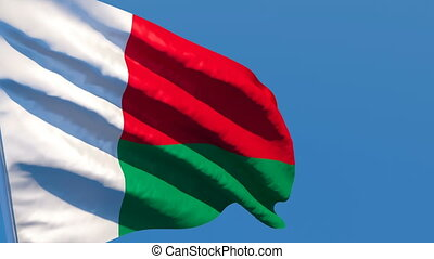 The national flag of Madagascar flutters in the wind against...