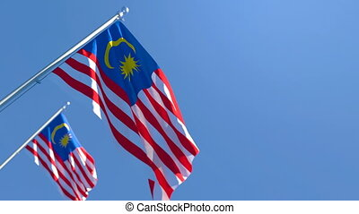 The national flag of Malaysia is flying in the wind against ...