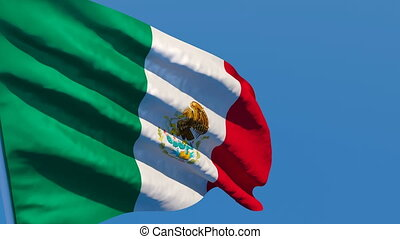 The national flag of Mexico flutters in the wind against a blue sky