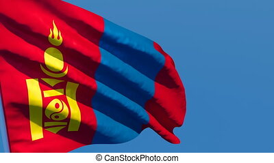 The national flag of Mongolia flutters in the wind against a blue sky