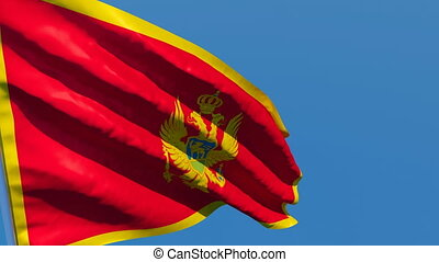 The national flag of Montenegro flutters in the wind against...