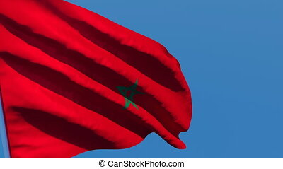 The national flag of Morocco flutters in the wind against a blue sky