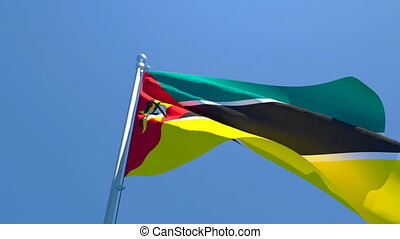 The national flag of Mozambique flutters in the wind against a blue sky