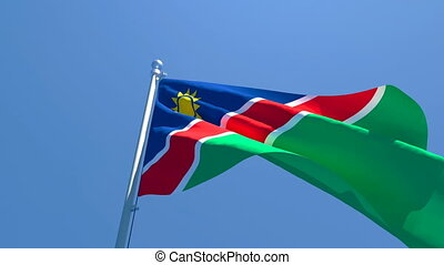 The national flag of Namibia flutters in the wind against a blue sky