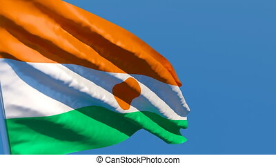 The national flag of Niger flutters in the wind against a ...