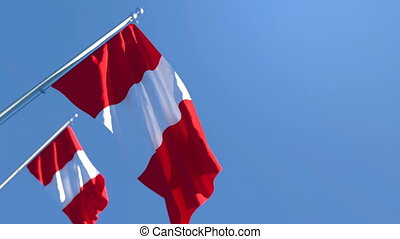 The national flag of Peru flutters in the wind against a blue sky
