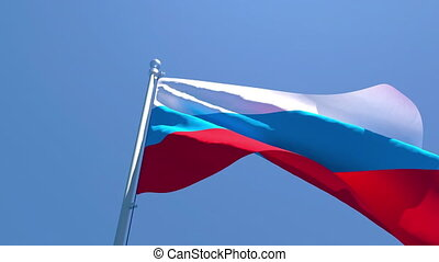The national flag of Russia is flying in the wind against a blue sky