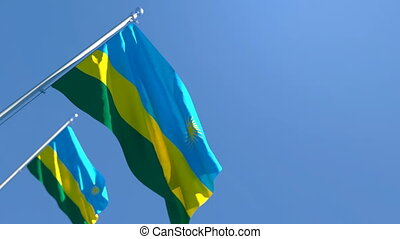 The national flag of Rwanda flutters in the wind against a blue sky