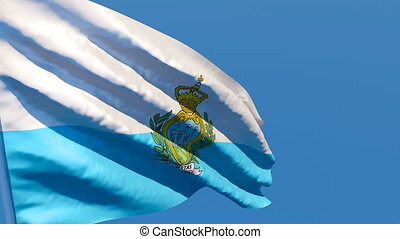 The national flag of San Marino flutters in the wind against a blue sky