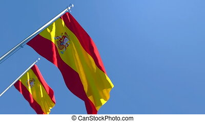 The national flag of Spain is flying in the wind against a blue sky
