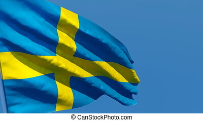 The national flag of Sweden flutters in the wind against a blue sky