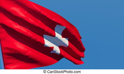The national flag of Switzerland flutters in the wind against a blue sky