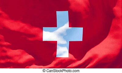 The national flag of Switzerland flutters in the wind.