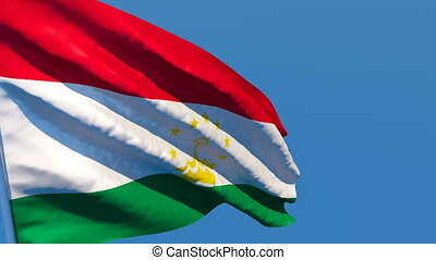 The national flag of Tajikistan flutters in the wind against...