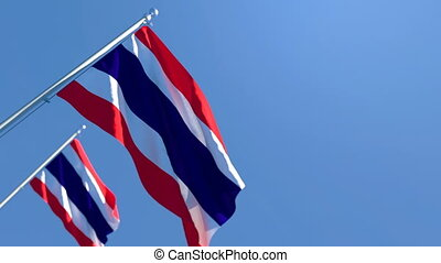The national flag of Thailand flutters in the wind against a blue sky