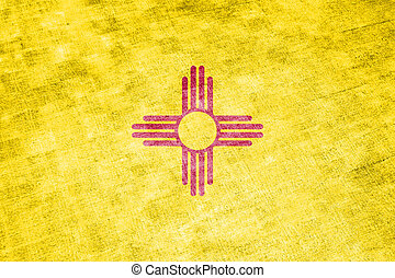 The national flag of the US state New Mexico in against a gray textile rag on the day of independence in different colors of blue red and yellow. Political and religious disputes, customs and delivery.