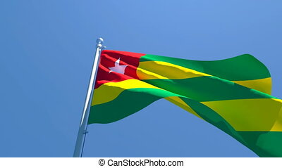 The national flag of Togo flutters in the wind against a blue sky.