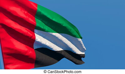 The national flag of UAE flutters in the wind against a blue...