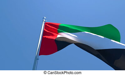 The national flag of UAE flutters in the wind against a blue sky