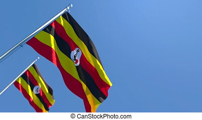 The national flag of Uganda flutters in the wind against a blue sky