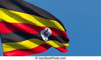 The national flag of Uganda flutters in the wind against a blue sky.