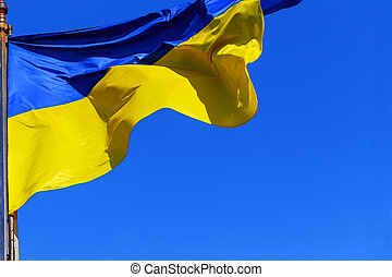 The national yellow and blue flag of Ukraine over clouds