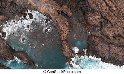The natural pools of the island of Tenerife are a secret place. Aerial view. Cliffs of frozen lava and turquoise ocean