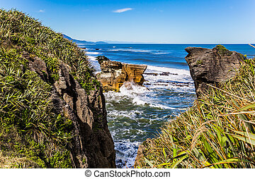 """The natural wonder of Paparoa Park, narrow fjord among unique """"pancake"""" rocks. Scenic coastline, huge rocks. South Island, New Zealand. The concept of photo, ecological and active tourism"""
