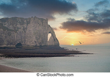 The needle in the chalk cliffs of the Normandy coast of Etretat, France, under a dramatic colorful sunset sky