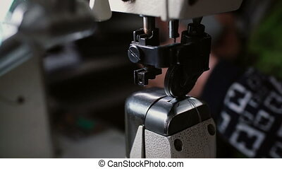 The needle of the sewing machine sews on a blue textile. Worker sews leather for shoe production.
