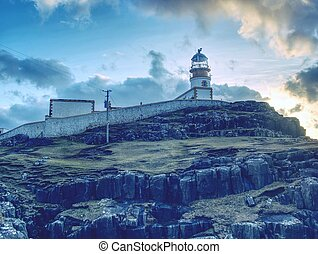 The Neist Point lighthouse on the end of  world. Foamy sea strikes against the cliff.