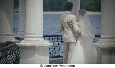 The newlyweds are in the gazebo with columns on the water.