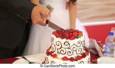 The newlyweds cut the cake garnished with fresh berries