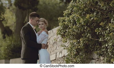 The newlyweds standing near a stone wall in the park