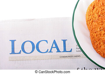 The newspaper with the name of heading Local and a plate with cookies.