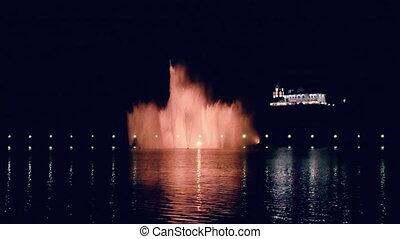 The night fountain is illuminated by beautiful lights on the embankment of the bay in the reflection of the calm water surface. Seamless Full HD looped footage with dark static river view.