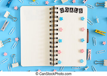 The notepad on the springs lies open. Next to the mess office supplies. The white pages of the notebook contain the inscription GOALS, pink and blue asterisks. Photo from the top on a blue background.