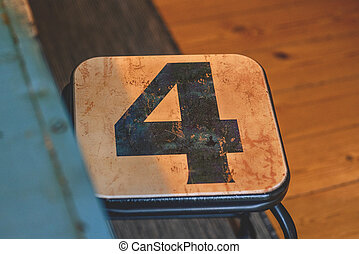 The number 4 on a small chair in a room