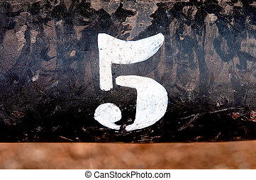 The number 5 on rusted old iron surface