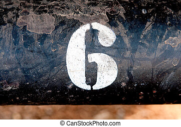 The number 6 on rusted old iron surface