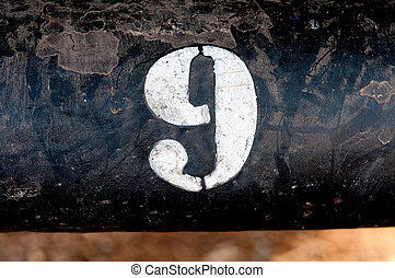 The number 9 on rusted old iron surface