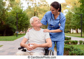 The nurse looks carefully at the old man, who is sitting in a wheelchair and smiling at him