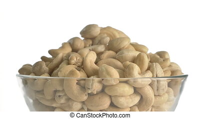 Nuts cashew turn on the white turntable. The subject white background is spinning and moving. The camera is static. On the table is a linen cloth bag. Shooting in 4k.