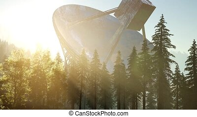 The observatory radio telescope in forest at sunset