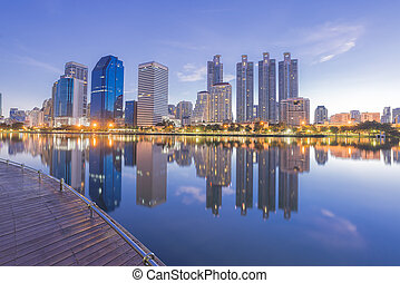The office building in the twilight scene reflection with the water in the pond at Bangkok city Thailand