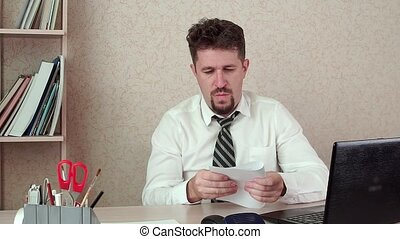 The office Manager of a bearded man bored at work, messing around with a stapler